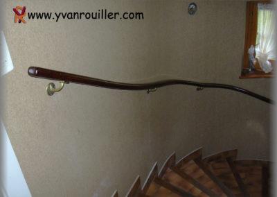 Main-courante en chêne teinté verni posée sur des cols de cygne laitonnés