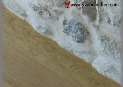 Ajustage parquet chêne verni contre le mur en pierre